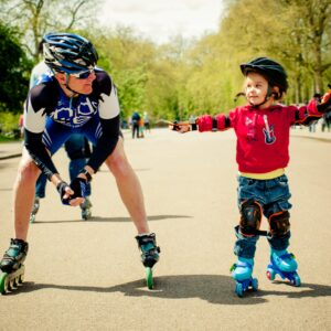 little boy rollerskating with his father