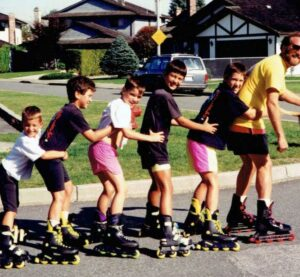 man-rollerskating-with-5-kids-hanging-from-his-waist